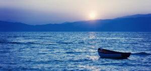 Liten träbåt på havet i en disig solnedgång