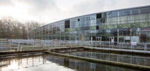 Reningsverkets vattenbassänger med en glasbyggnad i bakgrunden