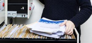 Person sorterar in dokument i ett arkivskåp.