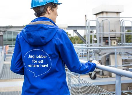 Person står med ryggen till med blå jacka med text Jag jobbar för ett renare hav.