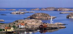 Vy över Fjällbacka med stugor och segelbåtar på västkusten.