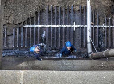 Två personer i skyddshjälm står på botten av en tömd reningsbassäng och tittar upp.