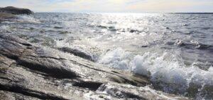Vågor slår mot klippor vid havet.