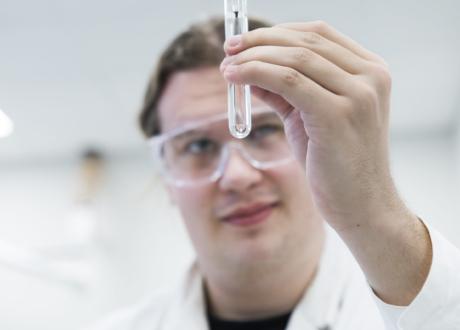 Labbtekniker tittar på vätska i ett provrör som han håller upp.