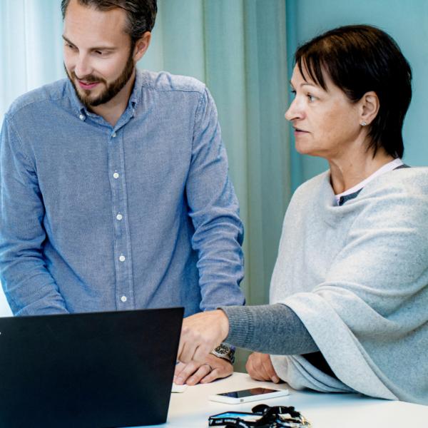 Tre personer på ett ljusblått kontor samtalar och tittar på en dator