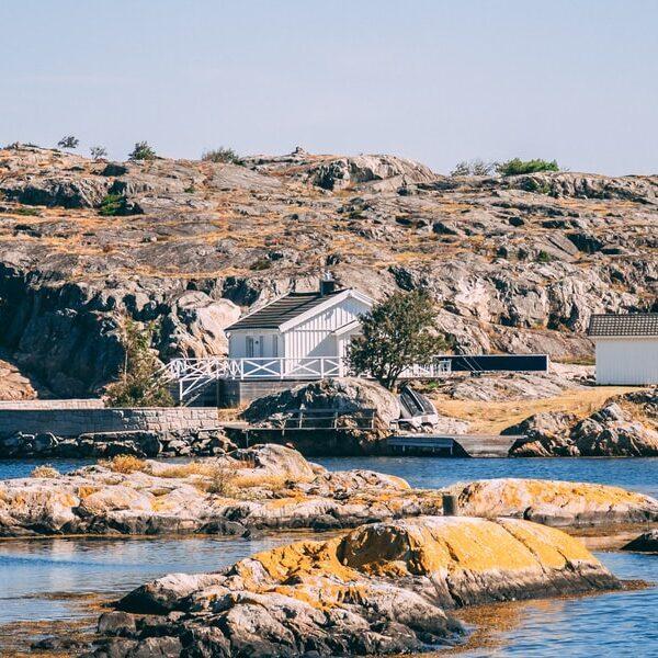 Vitt hus byggt på klipporna i skärgårdsmiljö.