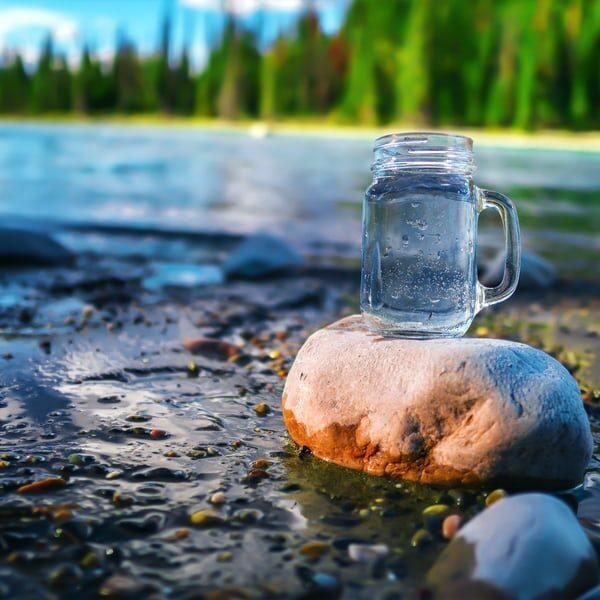 Fyllt vattenglas står på en sten vid en flod med skog i bakgrunden.