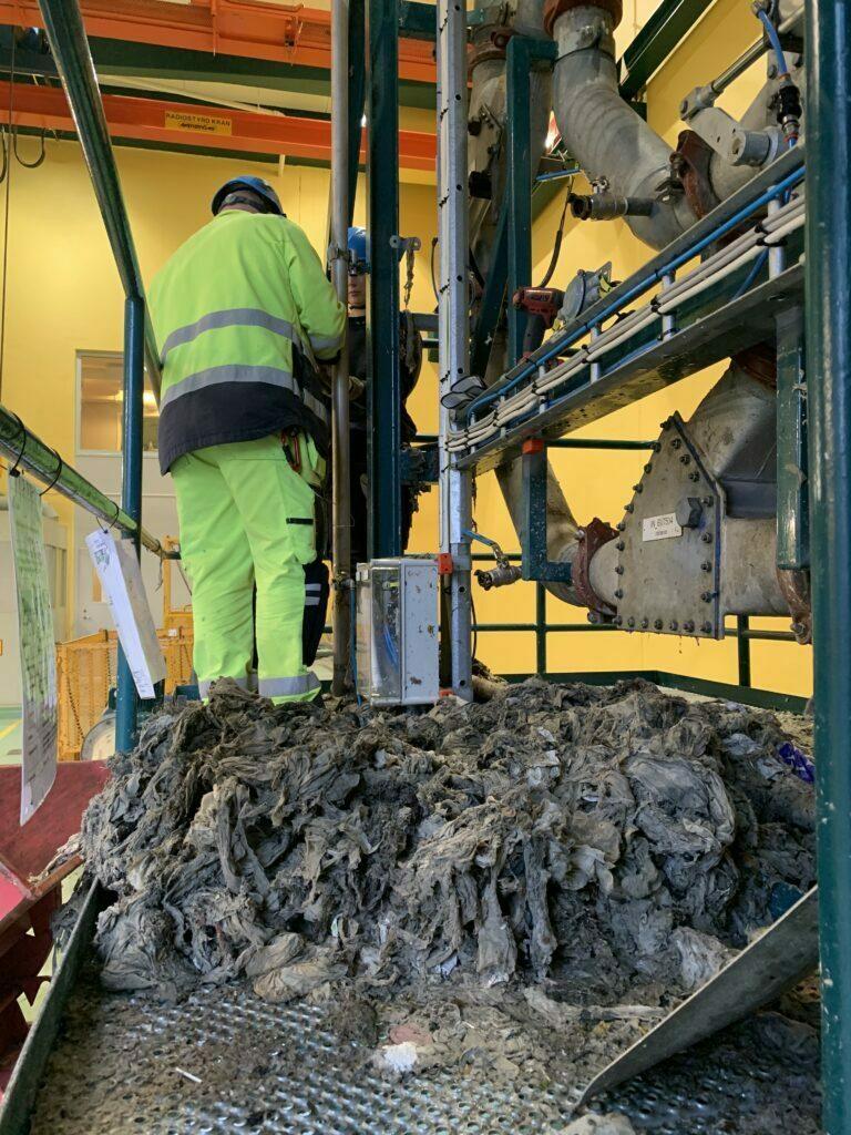 Man i gula arbetskläder skruvar på rörledningar. Stor hög av smutsiga våtservetter i förgrunden.