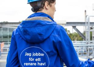 Blåklädd person står med ryggen med texten Jag jobbar för ett renare hav på jackan.
