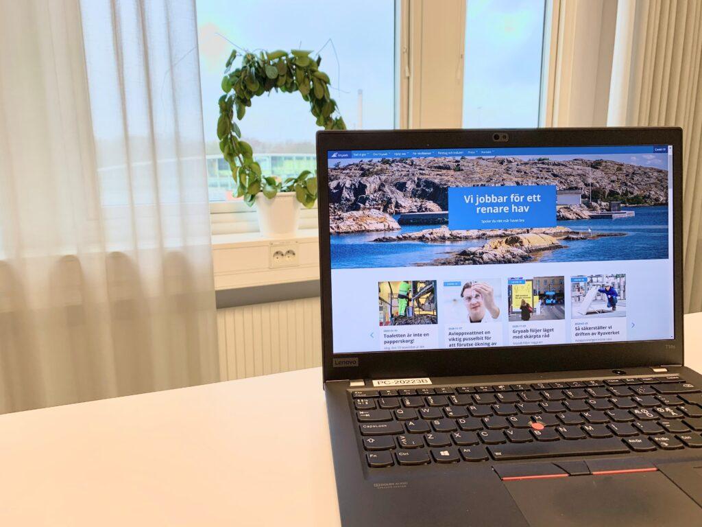 Bärbardator som visar Gryaabs webb på ett vitt skrivbord med fönster i bakgrunden.