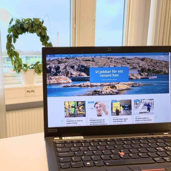 bärbar dator som visar Gryaabs nya startsida på ett vitt skrivbord med ett fönster i bakgrunden