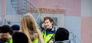 Kvinnlig guide står framför en grupp barn i reflexvästar utomhus.