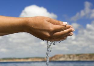 Närbild på vatten som rinner genom knäppta händer med havet i bakgrunden.
