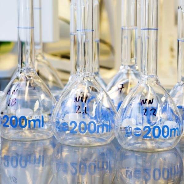 Flera glaskolvar utplacerade på en bänkskiva i Gryaabs laboratorium.