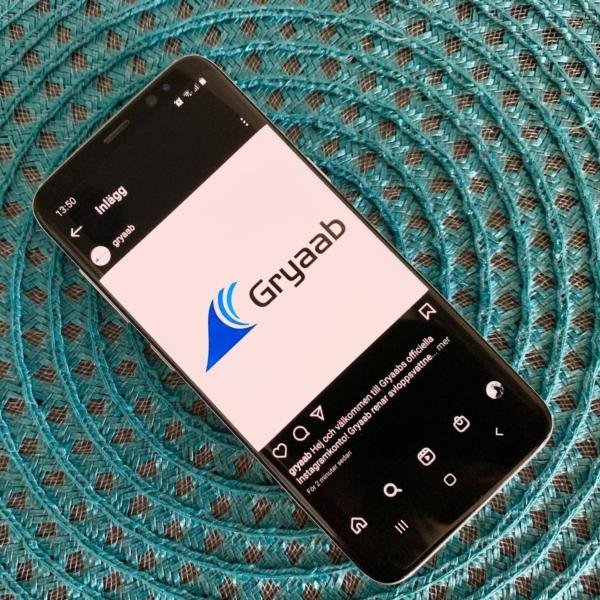 Telefon som visar Gryaabs instagramkonto på en blå bakgrund.