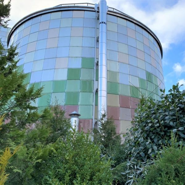 Gryaabs gröna och blåa biogasanläggning med gröna buskar framför.