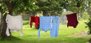 Kläder som hänger på tork på en tvättlina i en grönskande trädgård.