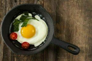 Ett stekt ägg, en delad körsbärstomat och en persiljekvist i en liten stekpanna.
