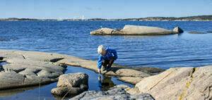 Blond pojke sitter på klippa med ett finger i vattnet.