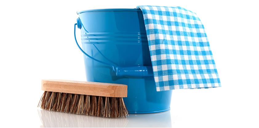 En blå skurhink med en blåvit rutig trasa hängandes över kanten samt en skurborste