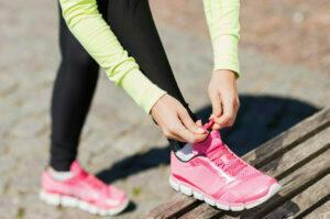 Kvinna i träningskläder som knyter skorna mot en bänk.