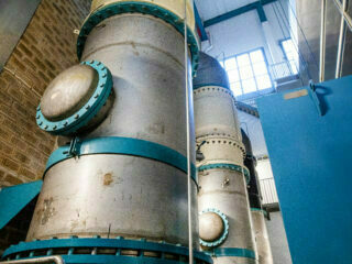 Tjocka rör inuti en byggnad där vattnet pumpas upp till reningsverket.